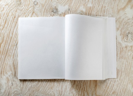 mockup: Blank opened book on light wooden background with soft shadows. Mock-up for graphic designers portfolios. Top view. Stock Photo