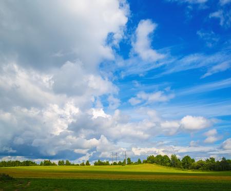 Heldere blauwe hemel met stapelwolken en een veld met groene gras. Kleurrijke zomer landschap. Stockfoto