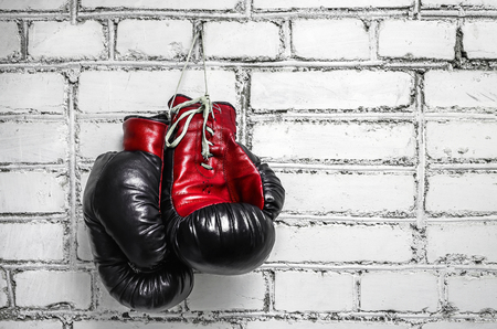 quiting: A pair of old boxing gloves hanging against a white brick wall. Stock Photo