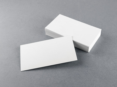 Photo of blank business cards with soft shadows on gray background. For design presentations and portfolios. Mock-up for branding identity. Standard-Bild