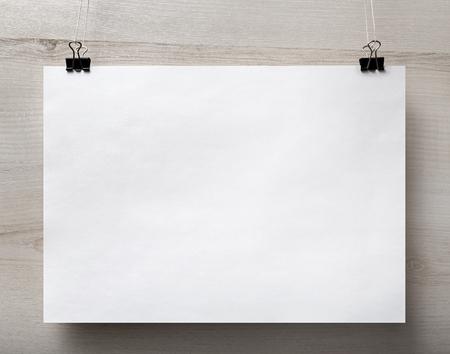 El cartel en blanco de papel blanco que cuelga en el fondo de madera clara. Para las presentaciones de diseño y carteras. Vista frontal.