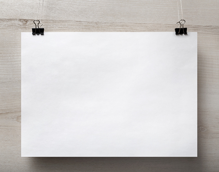 Blank white paper poster hanging on light wooden background. For design presentations and portfolios. Front view. Standard-Bild