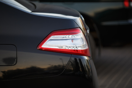 taillight: Closeup of a taillight on a modern black car with reflection. Shallow depth of field. Selective focus.