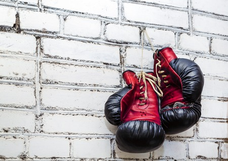 boxing glove: A pair of old boxing gloves hanging on white brick wall background.