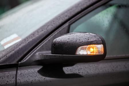 Close-up fragment zwarte auto met regen druppels. Moderne auto zijspiegels met richtingaanwijzer. Ondiepe scherptediepte. Selectieve aandacht.