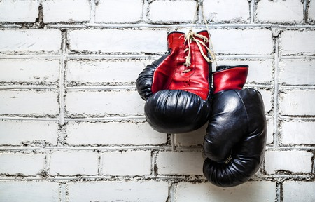 Pair of old red and black boxing gloves hanging on white brick wall.