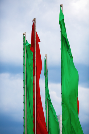 flagpoles: Flagpoles with vertical green and red flags against a blue sky. Vertical shot. Stock Photo