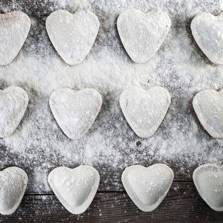 semimanufactures: Cooking ravioli. Heart shaped dumplings, flour and rolling pin on wooden background. Top view. Stock Photo