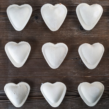 semimanufactures: Heart shaped ravioli on a dark wooden background closeup. Cooking dumplings. Top view.