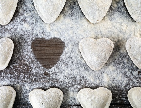 semimanufactures: Heart shaped ravioli sprinkle with flour, on wooden background. Cooking dumplings. Top view. Uncooked ravioli hearts Stock Photo