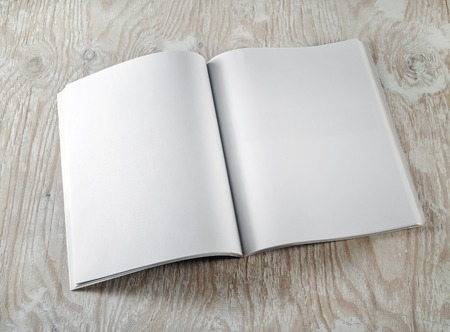 book pages: Photo of blank opened brochure on light wooden background. Template for graphic designers portfolios. Top view. Stock Photo