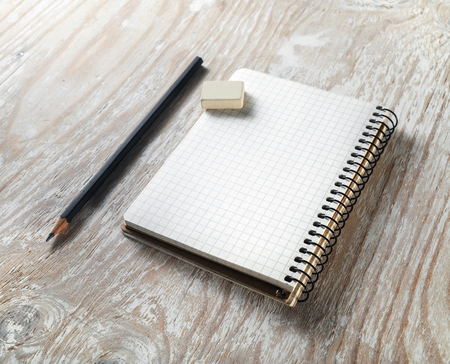 office supply: Photo of blank notepaper with pencil and eraser on light wooden background. Template for graphic designers portfolios. Mock-up for branding identity.