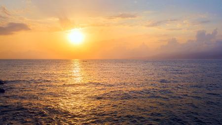 toned image: Beautiful seascape at sunrise. Sun reflection in sea water at dawn. Panoramic shot. Toned image.