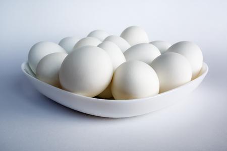 Foto van witte eieren op een witte vierkante schotel op een lichte achtergrond.