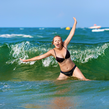 Young woman in a bikini bathing suit enjoying a dip in the sea waves. Girl on aqua background. Bright sunny day. Selective focus.