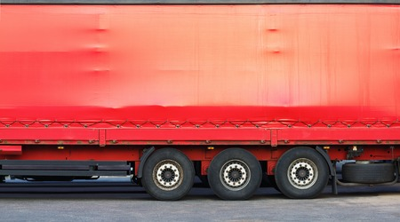 long haul journey: Close-up of the side of a big red truck. Space for text or image.