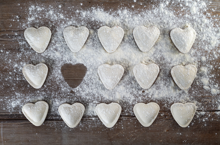 semimanufactures: Heart shaped ravioli sprinkle with flour, on wooden background. Stock Photo