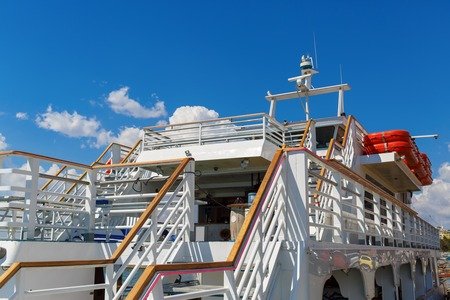 lifeboats: Close-up fragment of the deck with stairs white cruise ship on a background of blue sky with clouds.