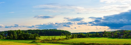 farmhouses: Sky with clouds, grass field, trees and farmhouses. Panoramic shot.