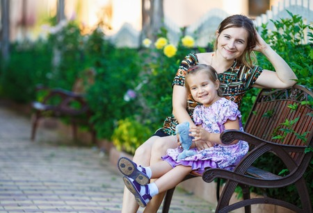 mother on bench: Mother and little daughter sit on a park bench on a background of bright green foliage. Stock Photo