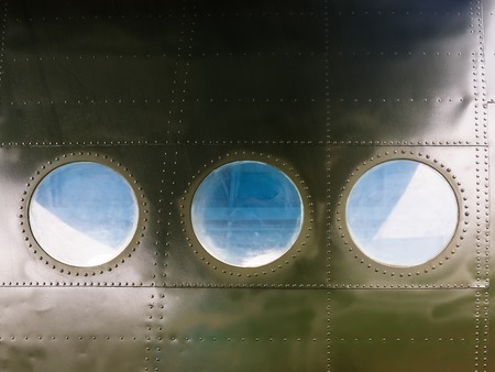 aircraft rivets: Portholes on military green painted metal background with rivet. Three portholes on board old retro airplane. Outside view of the old aircraft.