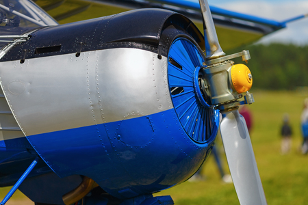 private parts: Engine and propeller of blue airplane. Close-up of a single-engine plane fuselage. Fragment of the aircraft.