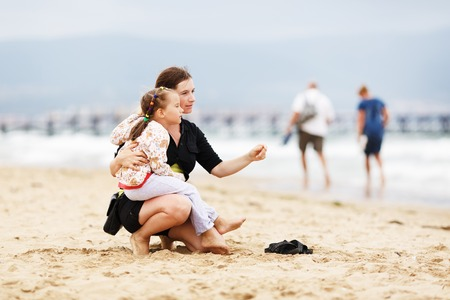 hugging knees: Pretty young mother sitting on the beach and holding his little daughter on his knee. Shallow depth of field. Selective focus.