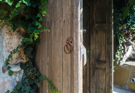 Old weathered wooden door with rusty handle. Rustic door. Shallow depth of field. Selective focus.