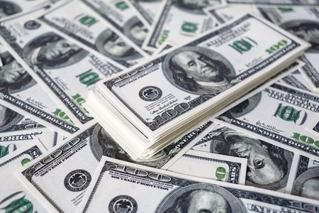 fake money: Close-up of a stack of one hundred dollar bills on a background of money. Fake money. Shallow depth of field. Selective focus. Stock Photo