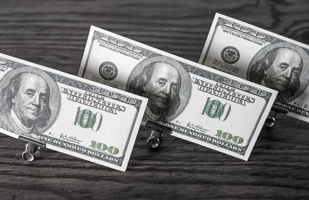 fake money: Hundred dollar bills in paper clips standing on a dark wooden background. Money in the paper clips. Fake money.