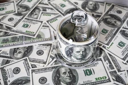 dinero falso: Dinero en un recipiente de vidrio en el fondo de billetes de cien dólares. Dinero falso. Foto conceptual sobre el tema de negocios. enfoque selectivo. Foto de archivo