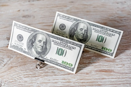 fake money: Money in the paper clips.One hundred dollar bills in paper clips standing on a dark wooden background. Fake money.