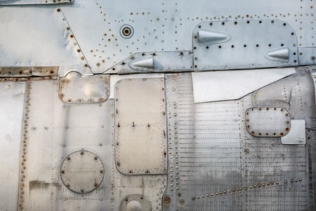 sheathing: Abstract metal background. Old weathered silver metallic background. Vintage metal texture with rivets and bolts. Sheathing old plane. Old metal texture.