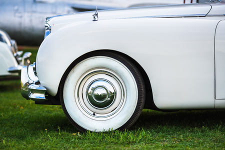 fender: Close-up of the front part of the old white retro car. Fender and the front wheel of the car. White vintage car. Side view. Selective focus.