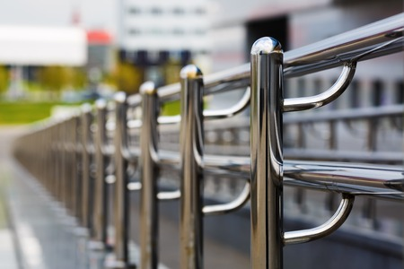 metal handrail: Chromium metal fence with handrail. Chrome-plated metal railings. Shallow depth of field. Selective focus. Stock Photo