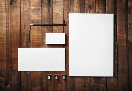 白紙のひな形は、木製のテーブル背景に設定。コーポレート ・ アイデンティティのテンプレートです。レターヘッド、名刺、封筒、鉛筆。デザイナ