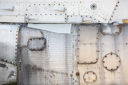 sheathing: Vintage metal texture. Weathered metallic background. Old vintage metal background with rivets and bolts. Sheathing old airplane.