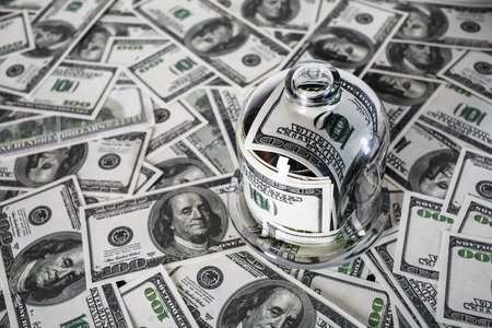 fake money: Money in a glass jar on the background of one hundred dollar bills. Fake money. Conceptual photo on the business theme. Shallow depth of field. Selective focus. Stock Photo