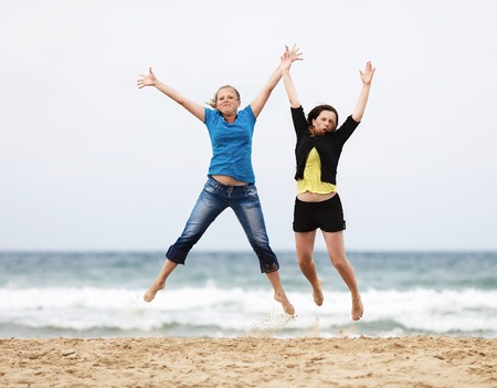 naughty or nice: Happy girls jumping outdoors. Two happy young women jump on the beach against the sea and cloudless sky. Selective focus on the models.