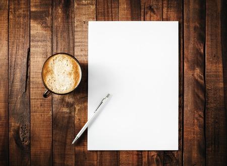Blanco branding sjabloon op vintage houten tafel achtergrond. Briefhoofd, koffiekop en pen. Blanco briefpapier. Mock-up voor branding identiteit voor het ontwerp portefeuilles. Bovenaanzicht.