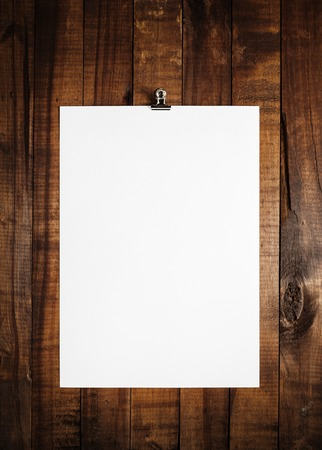 Blank sheet of paper on vintage wooden table background. White paper with plenty of copy space. Blank paperwork template for design portfolios. Top view.