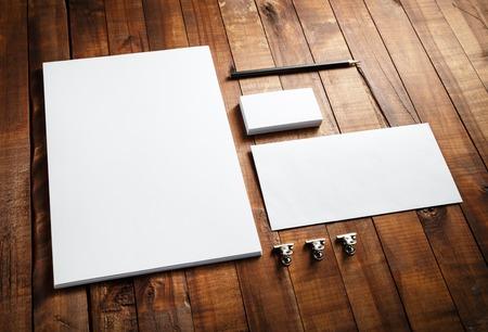 Puste papeterii i identyfikacja wizualna ustawiony na drewnianym stole rocznika tle: papier firmowy, wizytówki, koperty i ołówek. Puste makiety dla portfeli projektowych. Zdjęcie Seryjne