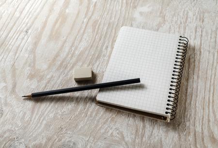 sketchbook: Blank sketchbook with a pencil and eraser on light wooden table background. Blank mock-up for design portfolios.
