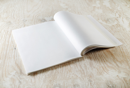 Blank magazine pages. Photo of blank opened magazine with soft shadows on wooden table background. Mock-up for graphic designers portfolios.