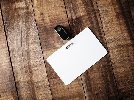 identification: Blank white plastic badge on vintage wooden table background. Responsive design template. Blank template for for ID. Mock-up for your design. Top view.