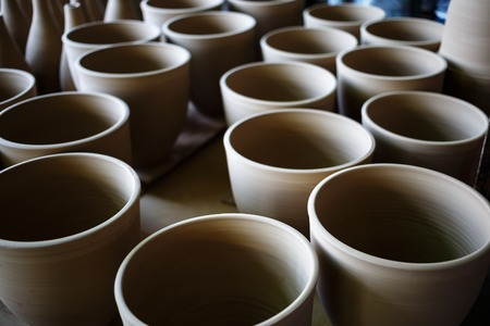 ware: Many rustic handmade terracotta clay pots ready to be fired. Shallow depth of field. Selective focus. Stock Photo