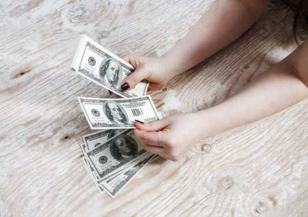 fake money: Woman hands with dollars on a wooden background. Cash in hands. Money in hands. Fake money. Shallow depth of field. Selective focus.