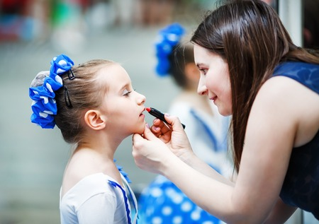 Mother putting lipstick on her daughter on mirror background. Mom helping little daughter to use lipstick before a dance performance. Mom makes make-up her daughter. Shallow depth of field. Selective focus. Stock Photo