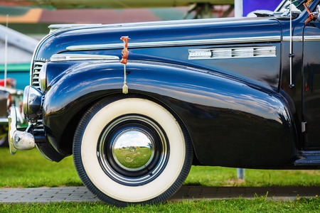 fender: MINSK, BELARUS - MAY 07, 2016: Close-up photo of black Buick Eight 1940 model year. Vintage retro auto. Fender and the front wheel of the car. Side view. Selective focus.