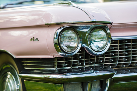 MINSK, BELARUS - MAY 07, 2016: Close-up photo of pink Cadillac de Ville. Detail on the headlight of vintage classic car. Selective focus.